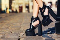 典雅的成套装备 特写镜头 时髦的黑皮革夏天鞋子 摆在老城市的街道上的时兴的女孩 女性 库存照片