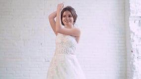 典雅的新娘,转动在宽敞的房间的长的白色豪华礼服的女孩根据窗口在软的灰色附近 股票视频