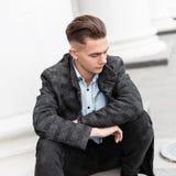 典雅的方格的灰色夹克的年轻时髦人士在时髦牛仔裤的一件时髦的衬衣有一种时兴的发型的休息 库存照片
