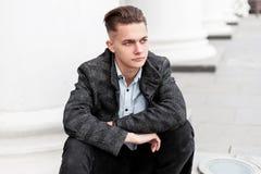 典雅的方格的灰色夹克的现代年轻人在时髦牛仔裤的一件时髦的衬衣有一种时兴的发型的休息 库存照片