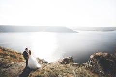 典雅的时髦的愉快的婚礼夫妇、新娘、华美的新郎海背景的和天空 免版税图库摄影