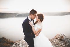 典雅的时髦的愉快的婚礼夫妇、新娘、华美的新郎海背景的和天空 库存图片