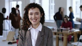 典雅的正装的愉快的白种人女性公司雇员有卷发的快乐地微笑在现代办公室的 股票录像