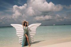 典雅的海滩的妇女给放松在马尔代夫海岛上穿衣 免版税库存照片