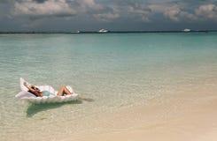 典雅的海滩的妇女给放松在马尔代夫海岛上穿衣 库存照片
