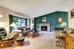 典雅的白色和绿色客厅 经典美国设计:砖壁炉、摇椅和五颜六色的沙发 免版税图库摄影