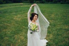 典雅的白色婚礼礼服的美丽的新娘与白色bouque 库存照片