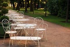 典雅的白色桌和椅子在庭院里在一个夏天晚上,空的等待的咖啡馆访客 图库摄影
