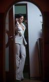典雅的白色衣服的年轻美丽的深色的妇女与站立在门框的长裤 摆在诱人的黑发的女孩户内 图库摄影