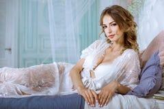 典雅的白色长袍的美丽的性感的夫人 图库摄影