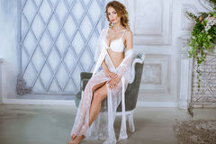 典雅的白色长袍的美丽的性感的夫人 免版税库存照片