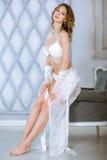 典雅的白色长袍的美丽的性感的夫人 免版税库存图片