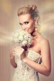 典雅的白色鞋带婚礼礼服的美丽的新娘 免版税库存图片