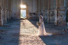 典雅的白色鞋带礼服的俏丽的新娘妇女有婚礼花束的 库存图片