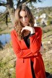 典雅的红色外套的美丽的少妇 库存图片