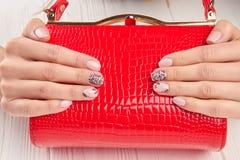 典雅的红色夫人提包在女性手上 免版税库存照片