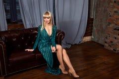典雅的绿色闪耀的礼服的美丽的性感的妇女金发碧眼的女人 与摆在黑暗的内部的长的腿的时装模特儿 免版税库存图片