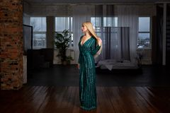 典雅的绿色闪耀的礼服的美丽的性感的妇女金发碧眼的女人 与摆在黑暗的内部的长的腿的时装模特儿 库存照片