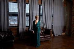 典雅的绿色闪耀的礼服的美丽的性感的妇女金发碧眼的女人 与摆在黑暗的内部的长的腿的时装模特儿 免版税库存照片
