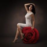 典雅的美丽的妇女和大红色罗斯 免版税库存照片