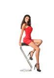 典雅的美丽的妇女坐一把当代金属棒凳子,隔绝在白色 库存图片