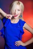 典雅的美丽的妇女白肤金发与在一件蓝色礼服的红色嘴唇在演播室 免版税库存照片