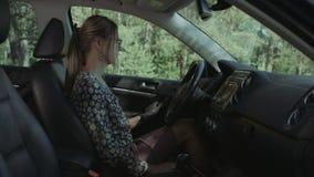 典雅的美丽的妇女紧固汽车座位传送带 股票录像