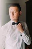 典雅的英俊的年轻时尚人画象白色衬衣和弓领带的 库存照片