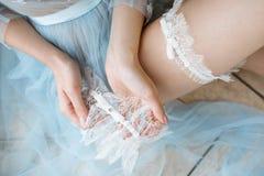 典雅的蓝色长袍和袜带的美丽的性感的夫人 库存照片