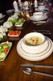 典雅的蜡烛点燃了晚餐用汤、菜和花 免版税图库摄影