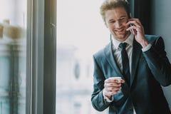 典雅的衣服的有快乐的人微笑和电话谈话 免版税图库摄影