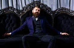 典雅的衣服的百万富翁坐豪华沙发 免版税库存照片