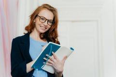 典雅的衣裳的兴旺的满意的女实业家在日志写,有高兴的表示,佩带眼镜,做名单计划 免版税图库摄影