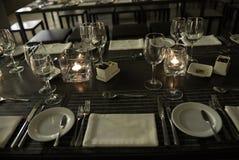 典雅的表集合,被点燃蜡烛,白色折叠了餐巾-现代餐馆 免版税图库摄影
