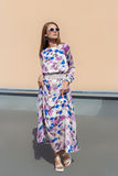 典雅的设计师礼服的美丽的年轻性感的女孩由在摆在的太阳镜的轻的织品制成在照相机 免版税库存照片