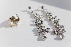典雅的豪华新娘耳环和婚戒 免版税库存照片