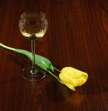 典雅的酒杯和郁金香在黑暗的木背景 图库摄影