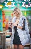 典雅的长的公平的有白色皮大衣的,室外射击头发年轻美丽的妇女在一个冷的冬日 可爱的白肤金发的女孩 免版税图库摄影