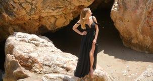 典雅的黑礼服的美女在岩石 股票录像
