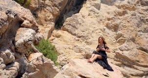 典雅的黑礼服的美女在岩石 影视素材