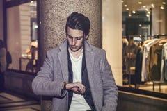 典雅的年轻人室外佩带的羊毛外套 免版税库存照片