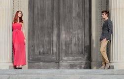 典雅的年轻夫妇由大木门分离了 库存照片