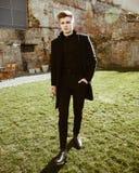 典雅的黑衣裳的年轻人 免版税库存照片