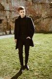 典雅的黑衣裳的年轻人 库存照片