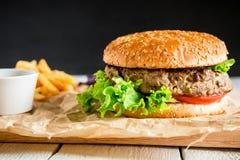 经典鲜美汉堡包用鲜美牛肉、调味汁和炸薯条在黑暗的背景 美国食物 库存照片