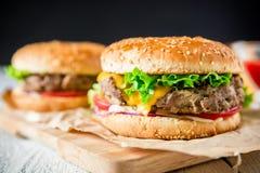 经典鲜美汉堡包用鲜美牛肉和调味汁在黑暗的背景 美国食物 免版税图库摄影