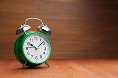 经典绿色在木backgroun的闹钟早晨唤醒的时间 免版税库存图片