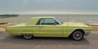 经典黄色雷鸟汽车在沿海岸区散步停放了 库存图片