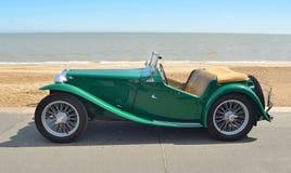 经典绿色MG跑车在沿海岸区散步停放了 免版税库存图片