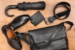 经典黑鞋子、公文包、传送带和伞在木地板上 库存照片